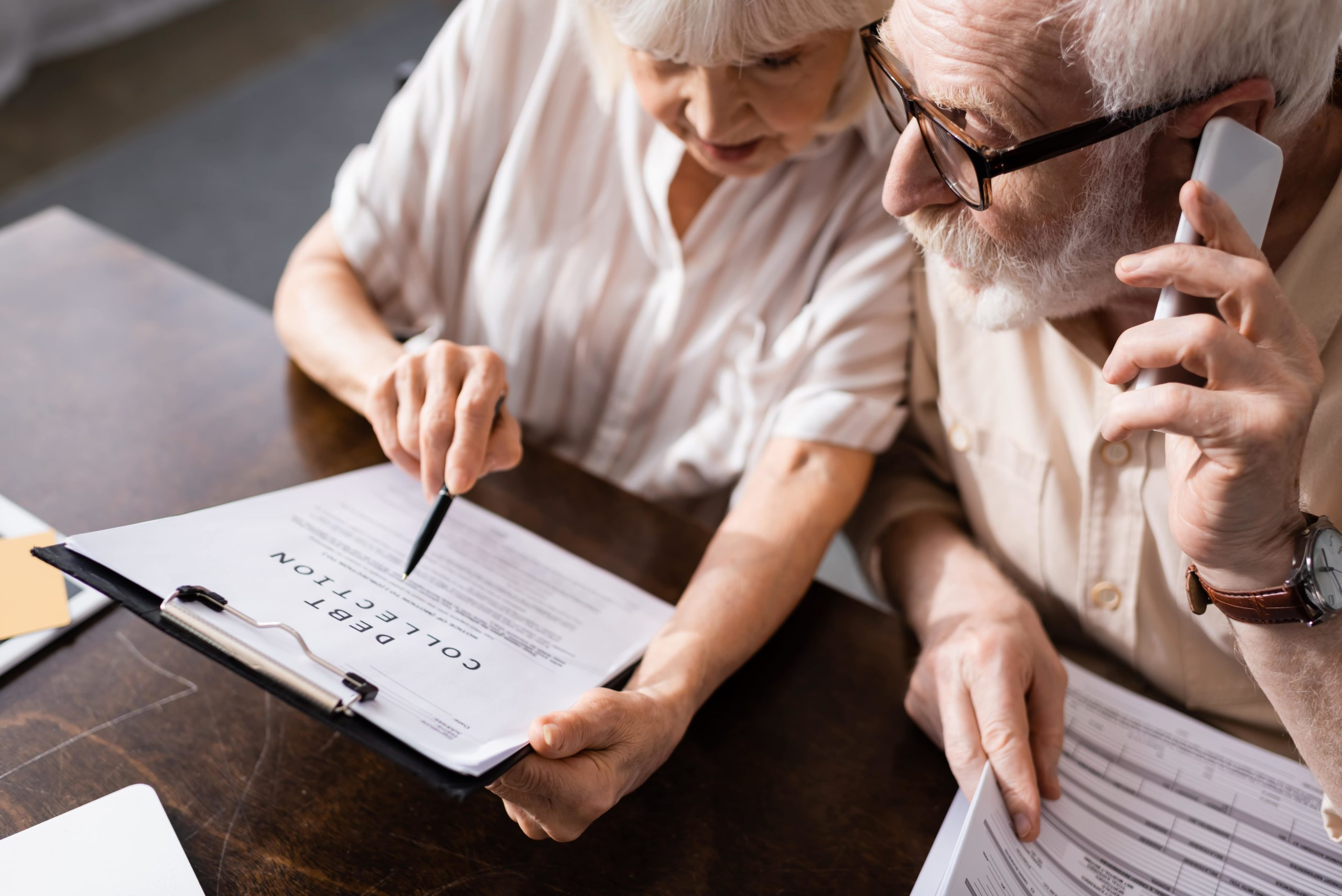 High angle view of elderly couple going over paperwork